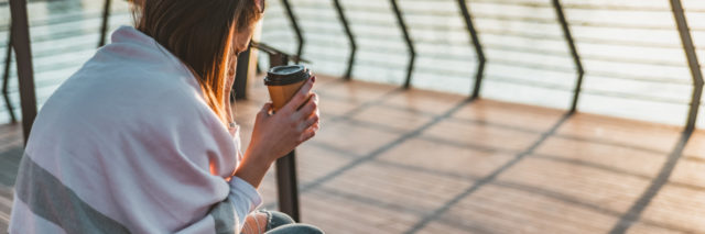 woman sitting with blanket near the water, holding coffee