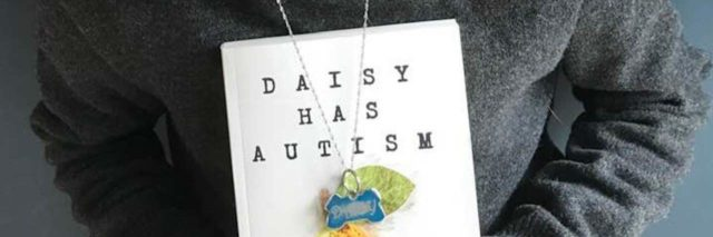 "Girl holding a copy of ""Daisy Has Autism"""