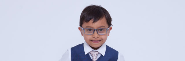 Little boy with Down syndrome looking sharp wearing a suit, hands on hips.
