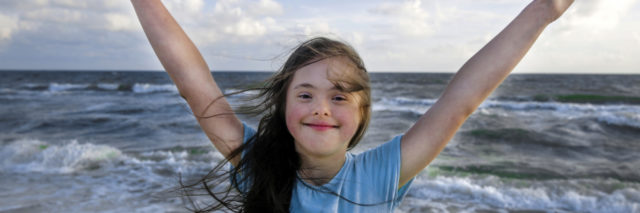 Girl with Down syndrome smiling with arms spread wide and ocean in the background