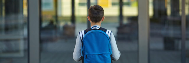 A young boy wearing a backpack looking at the front door of a school