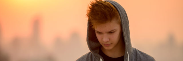 a teenage boy looking a his phone