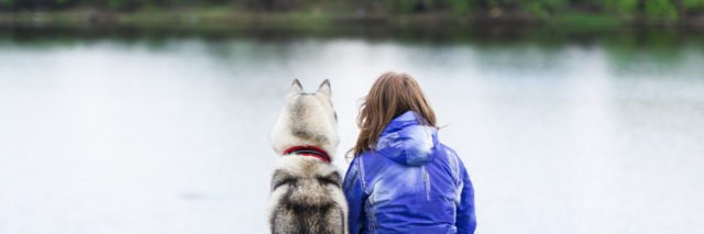 Dog and woman sit on the river bank.