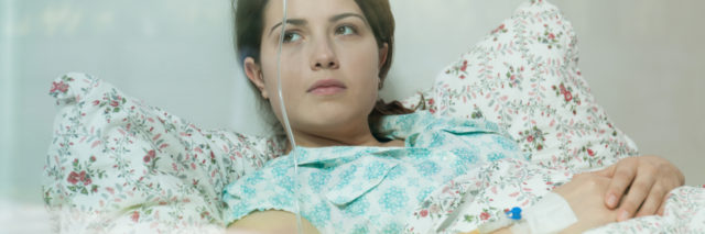 Ill young woman lying in hospital bed