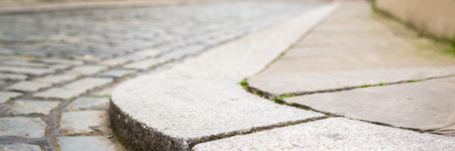 Curb on cobbled street