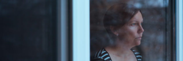 Woman standing by the window and looking outside