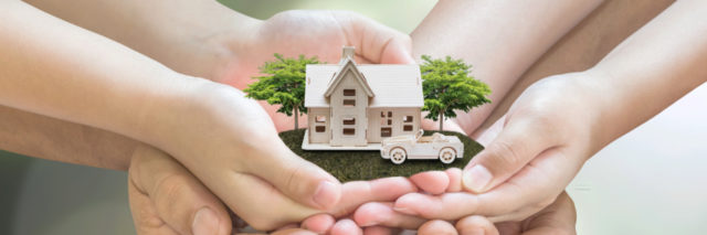 Hands holding miniature house.