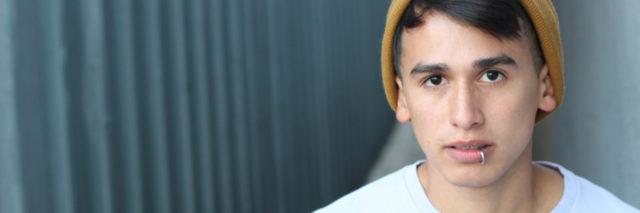 Un joven latino mira la camara con expresion grave. Tiene puesto una polera blanca. Tiene pelo negro. Tiene un anillo en su nariz.