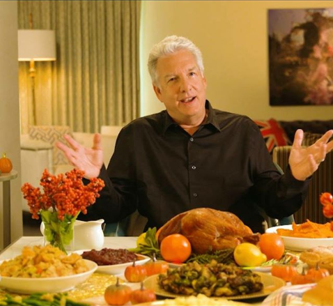 Marc Summers, television host, sits before a large feast. He has white hair. He is wearing a black dress shirt.
