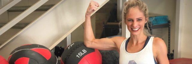 woman standing next to strength training equipment