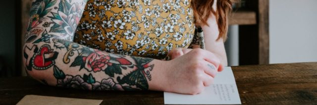 photo of redhead woman with tattoos writing a letter