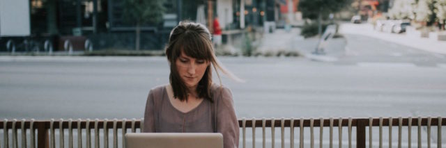 A woman on her lap top sitting outside at a cafe