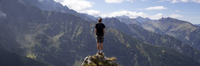 photo of man on top of mountain alone standing on rock