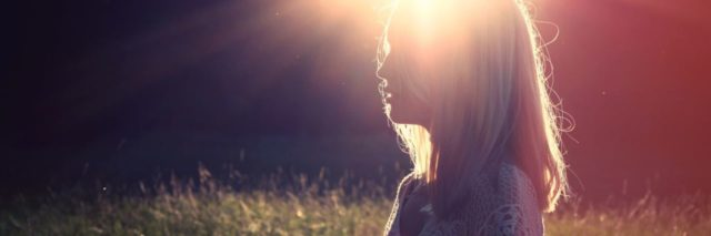 photo of woman silhouetted by sunlight and light flare