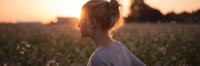 photo of woman with glasses standing in field at sunset