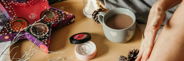 photo of assortment of self-care goods on wooden tray on bed with a woman's legs in shot, including tea, treats and lotions