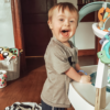 Shannon's son, a small boy with Down syndrome, blonde hair and a big smile, playing at home.