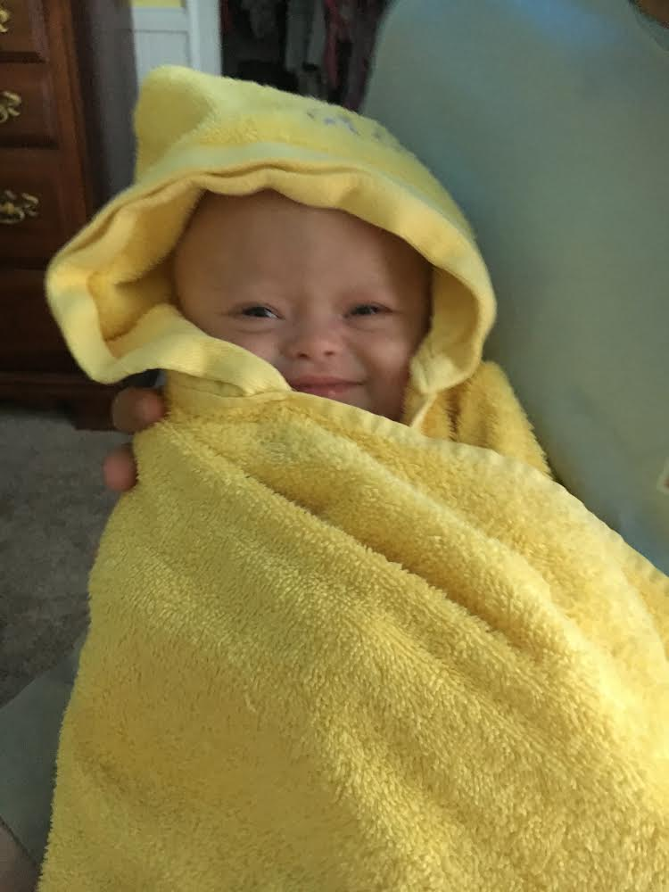Baby Alice wrapped in a yellow towel.