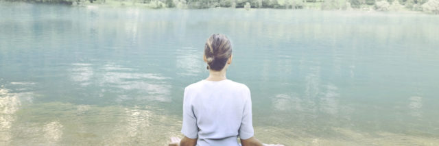 Woman doing yoga in front of a spectacular mountain lake.