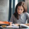Woman taking down notes in diary
