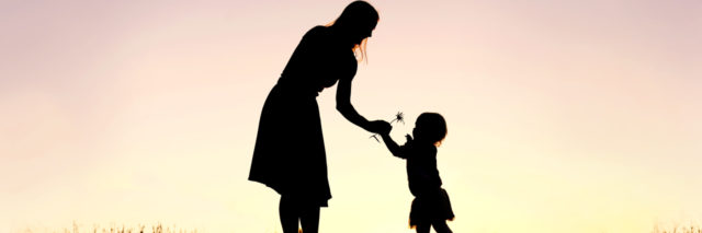 silhouette of a mom giving a little girl a flower