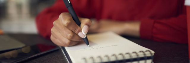 Woman writing in notebook.