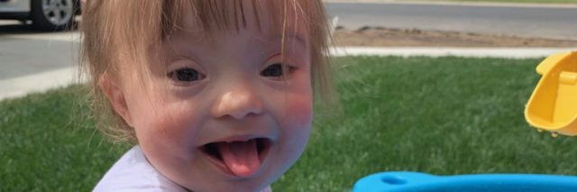 little girl with Down syndrome playing at a water table