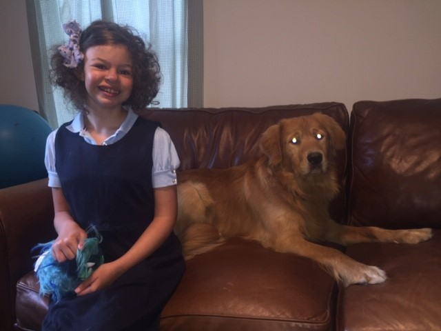 the author's daughter smiling, next to her dog