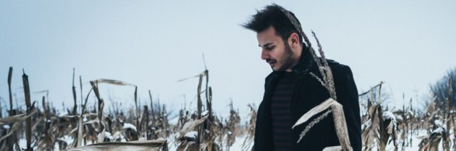 photo of man standing in winter cornfield
