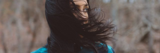 photo of woman with dark hair in woods with hair covering her lower face
