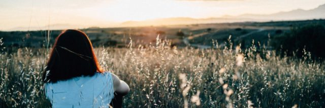 woman sitting in a field while the sun is setting