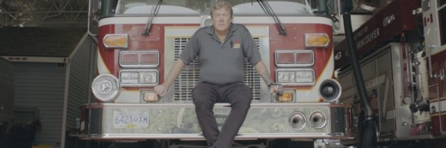photo of retired firefighter Erik Bjarnason sitting on firetruck looking at camera