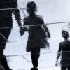 Blurry reflection of two children holding their parents hand