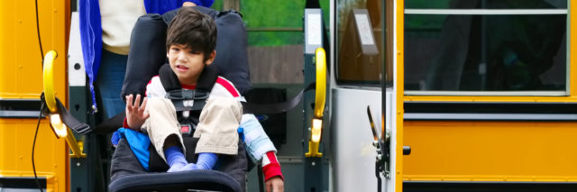 Boy in wheelchair on bus lift.