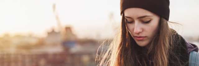 Young woman with long hair and a beanie looking down with a sunset background