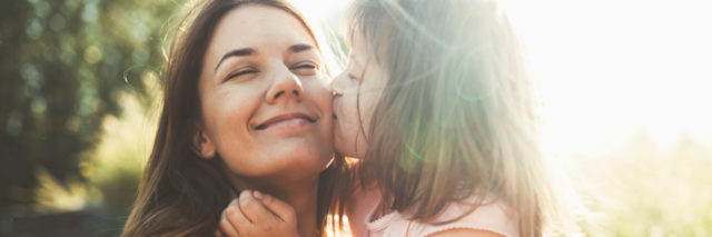 A young girl kissing her mom on the cheek