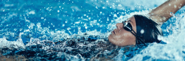 A woman swimming the backstroke in a pool