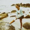 Woman on the beach holding her knee brace.