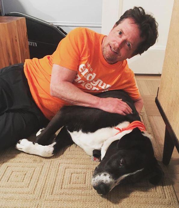 Michael J Fox wearing orange shirt while next to black and white dog