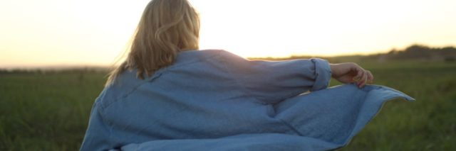 photo of blonde woman in field with window billowing shirt and sun behind her