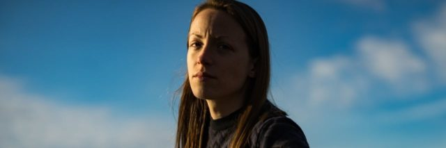photo of woman against blue sky looking serious into camera