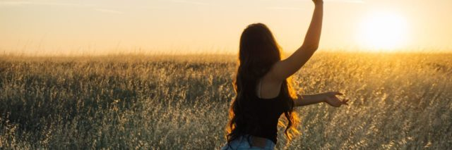 photo of woman dancing in rising or setting sun with arms stretched out, standing in field