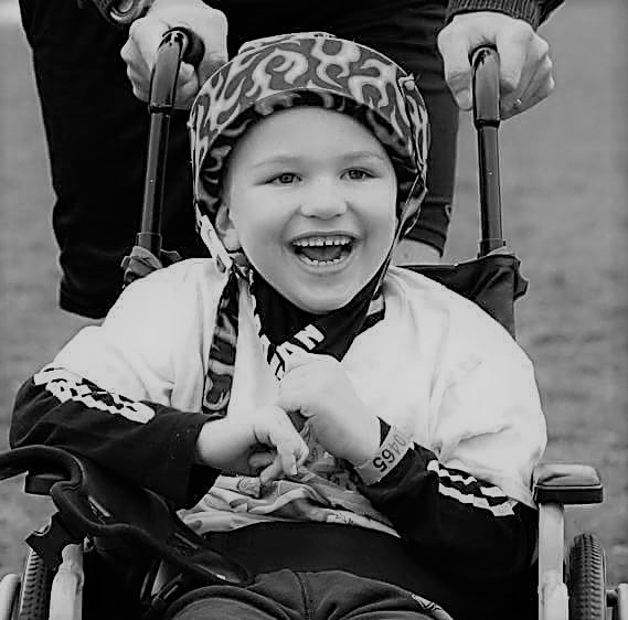 the author's son, Sam, smiling in his wheelchair