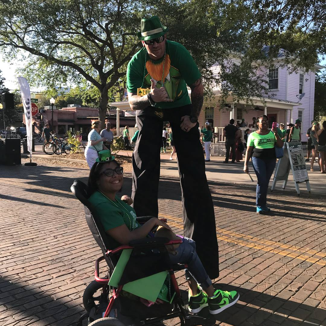 Tylia at a St.Patrick's Day festival with a performer on stilts.