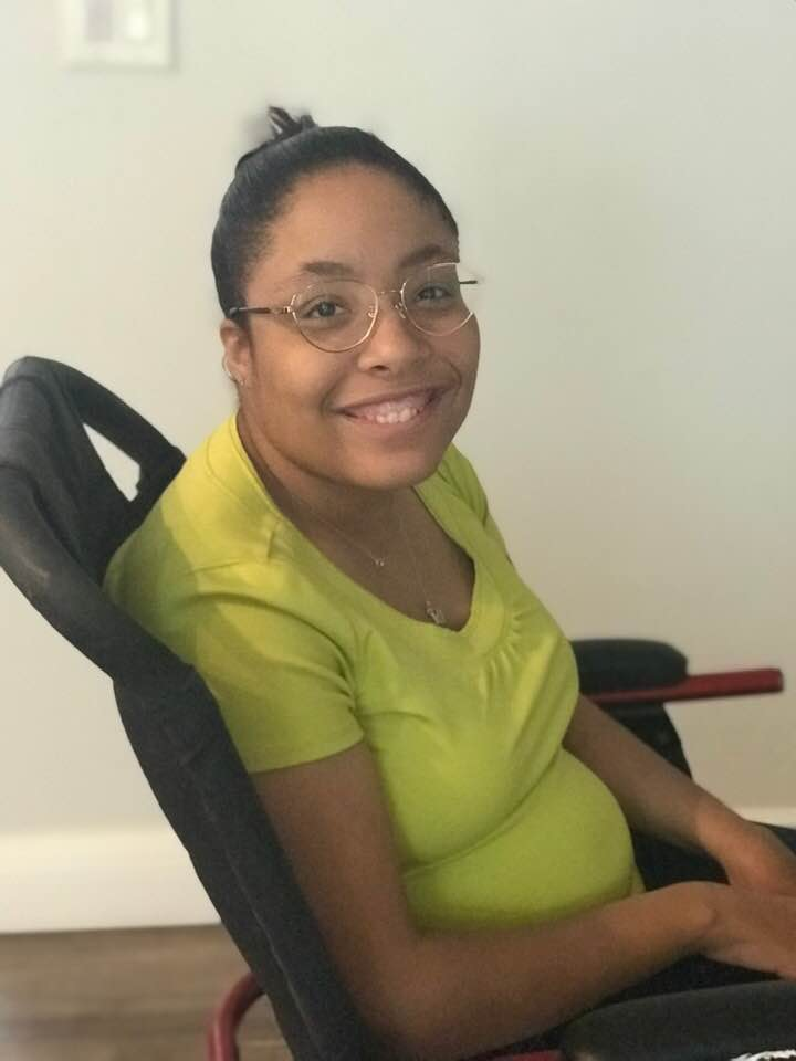 Tylia sitting in her wheelchair, smiling.