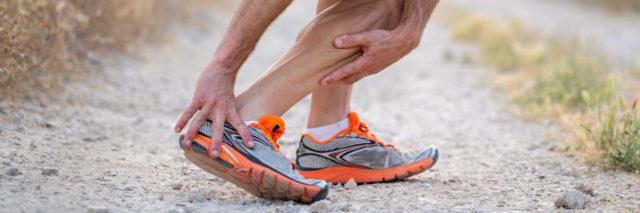 Man holding leg in pain.