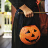 A child dressed as a witch holding a pumpkin shaped trick or treating bag