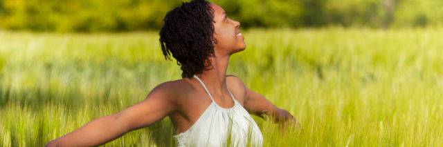 an African American woman standing and smiling in a field