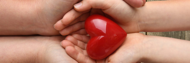an adult and child's hands holding a red heart