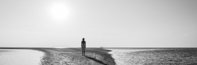 Silhouette of woman standing alone on small sand island.